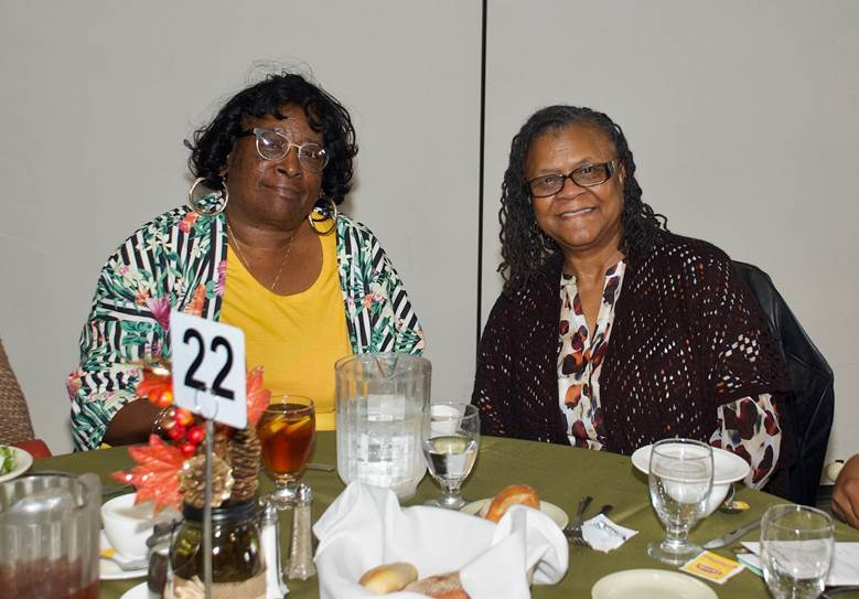Two Women Sitting On Table 22